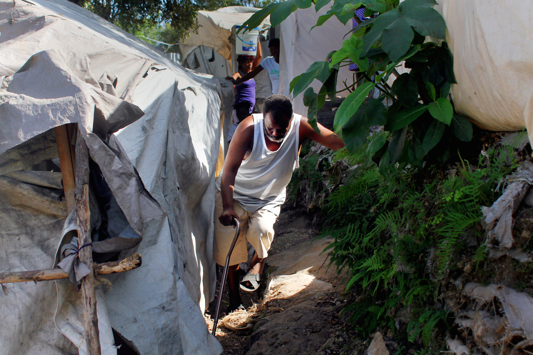 Charles Ivalien, 52, makes his way through the narrow, hillside paths of the Acra 2 camp in the Pétion-Ville commune of Port-au-Prince. The International Organization for Migration is in the process of clearing the camp, one of 271 still open since the 2010 earthquake displaced 1.5 million Haitians. Ivalien is now renting a home with a year-long subsidy provided by IOM.