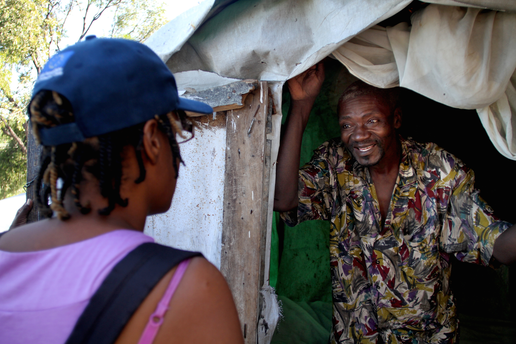 An IOM staff member speaks with Exelus Occima about relocation from his tent home in the Acra 2 camp. The former taxi driver lost his leg in an accident and had difficulties finding a handicap-accessible home.