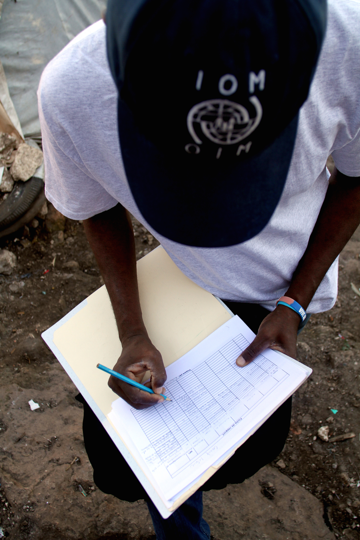 An IOM staff member takes notes while making rounds in the Acra 2 camp.