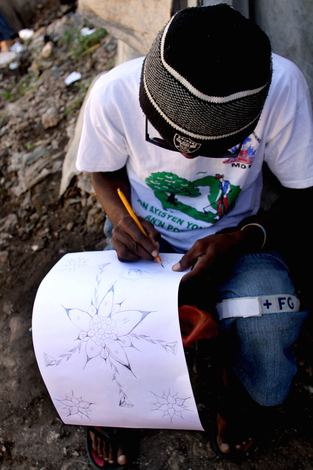 Acra 2 resident Gerry Bissainthe draws outside his tent in the camp.