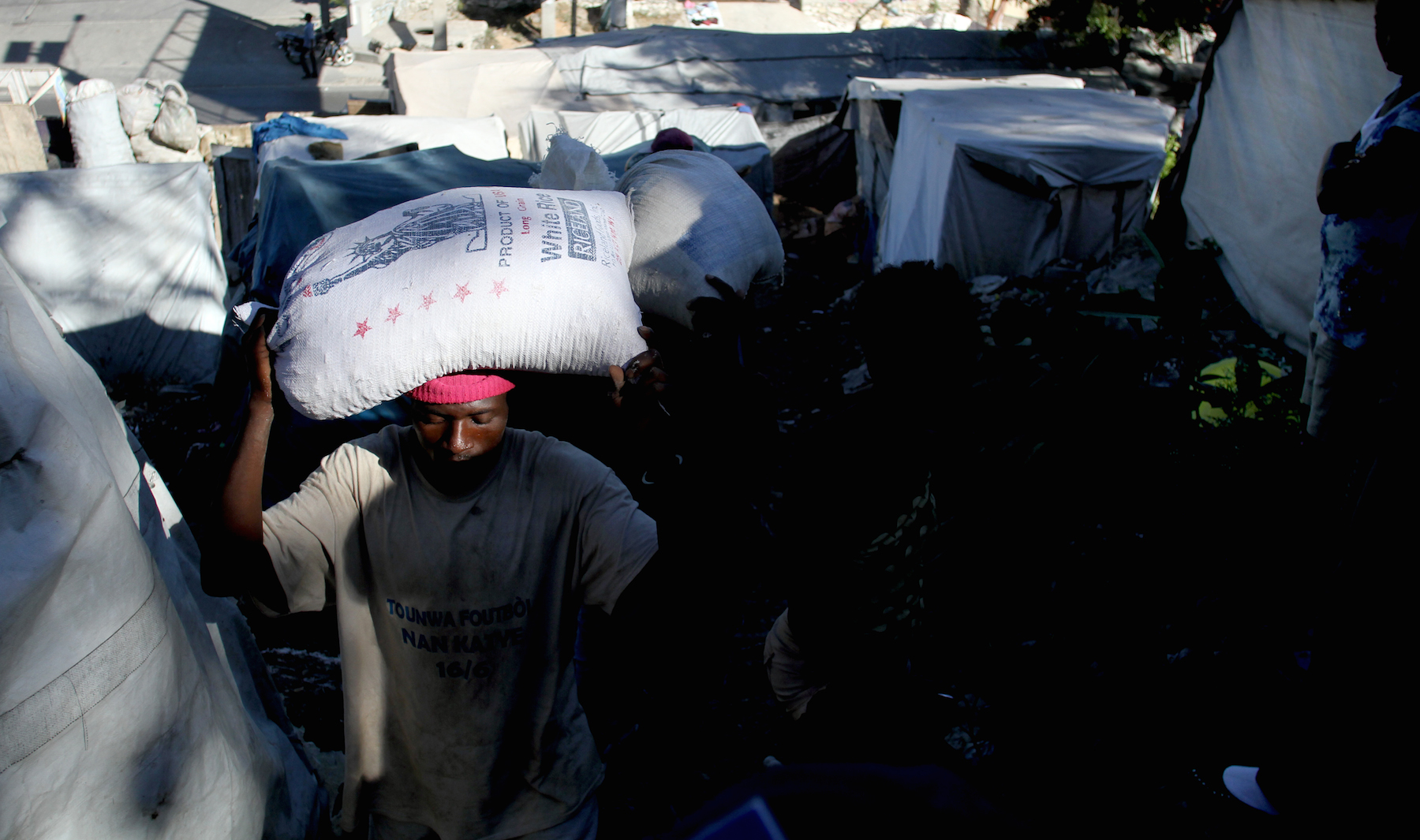 A man carries a bag of rice up the hills of the Acra 2 camp. Some critics of the humanitarian response in Haiti say that rice donated by the United States disrupts local food distribution and revenue streams.