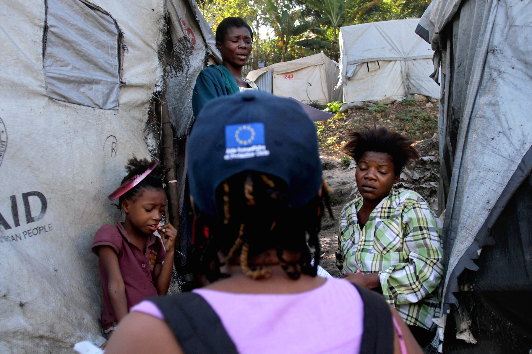 An IOM staff member speaks with camp residents about the relocation process.